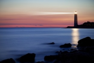 Lighthouse with beacon of light shining across the sea