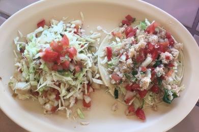 Grilled fish guarache covered in raw cabbage and pico de gallo alongside a crab soft taco with fresh lettuce and pico de gallo
